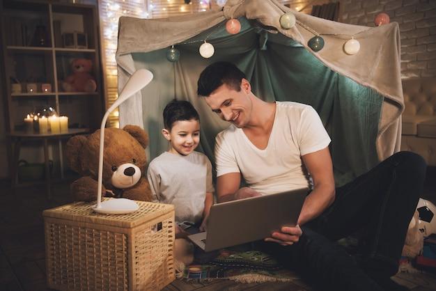 Vader en zoon kijken film op laptop 's nachts thuis