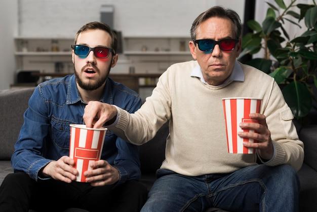 Vader en zoon kijken naar 3d-film in de woonkamer