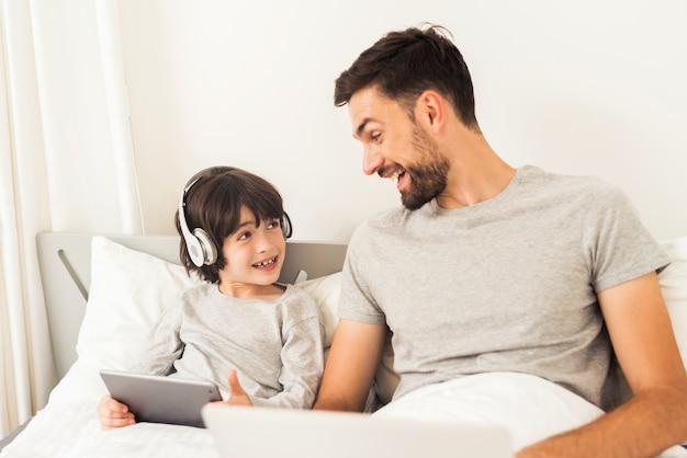 Vader en zoon kijken naar de laptop.