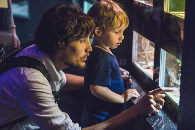 Vader en zoon kijken naar de vissen in het aquarium in oceanarium.