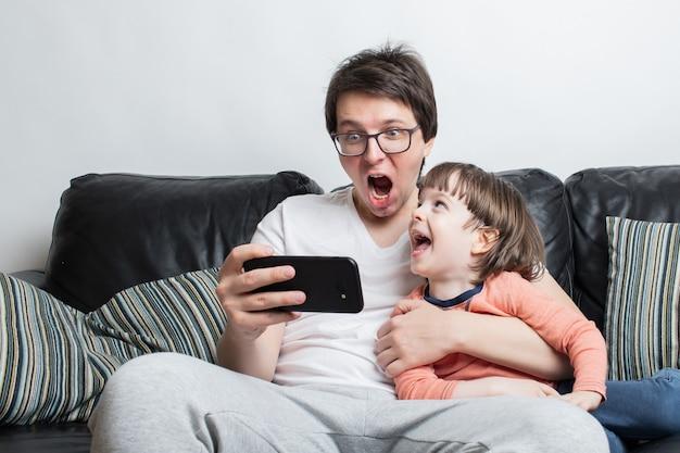 Vader en zoon kijken naar een enge video op de telefoon.