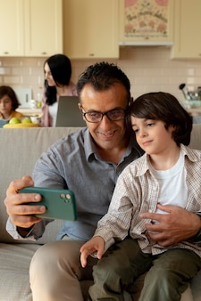 Vader en zoon kijken naar een smartphone thuis