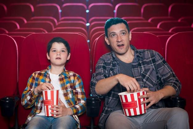 Vader en zoon kijken naar film in de bioscoop