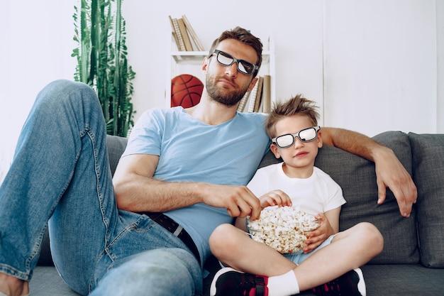 Vader en zoon kijken naar films thuis in 3d-bril en eten popcorn