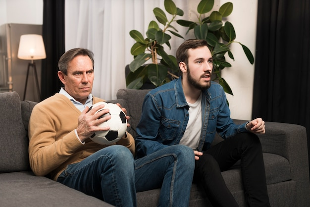 Vader en zoon kijken naar spel in de woonkamer