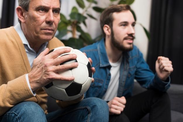 Vader en zoon kijken naar spel