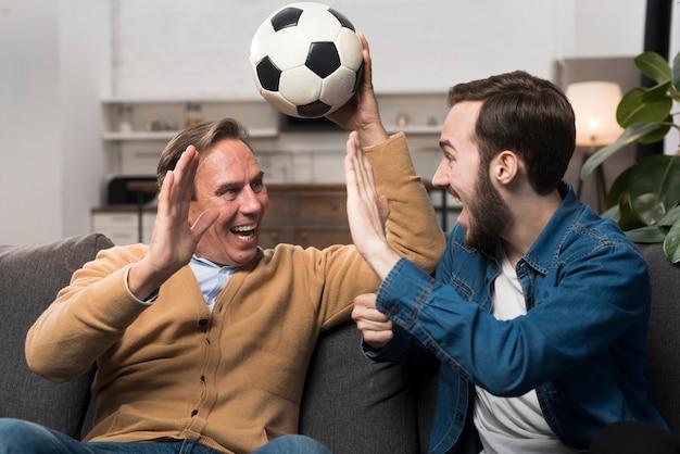 Vader en zoon kijken naar sport en juichen in de woonkamer