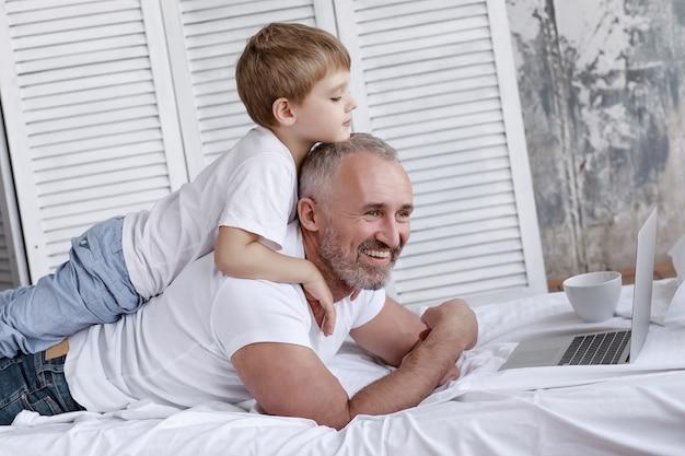 Vader en zoon kijken naar tekenfilms op een laptop die op het bed ligt