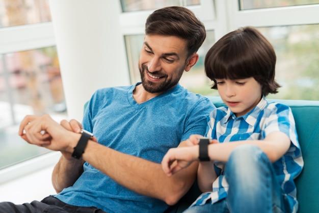 Vader en zoon kijken op het horloge. ze controleren de tijd.