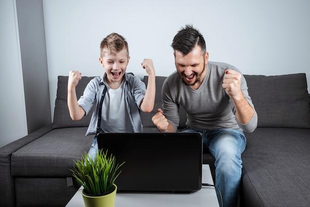 Vader en zoon kijken voetbal in een laptop thuis