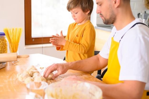 Vader en zoon kneden het deeg met blote handen zijaanzicht