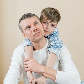 Vader en zoon knuffelen hem