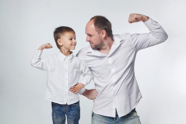 Vader en zoon laten de kracht van hun biceps zien. vaderschap, psychologie van relaties