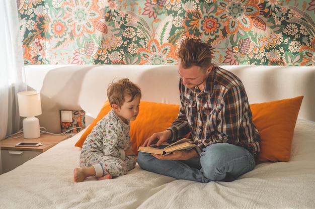 Vader en zoon lazen samen een boek, glimlachend en knuffelend. gezinsvakantie en saamhorigheid