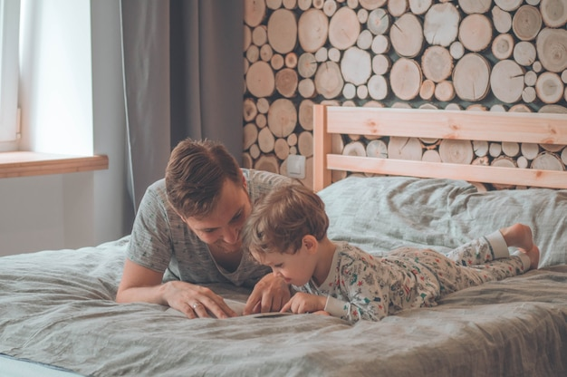 Vader en zoon lazen samen een boek, glimlachend en knuffelend