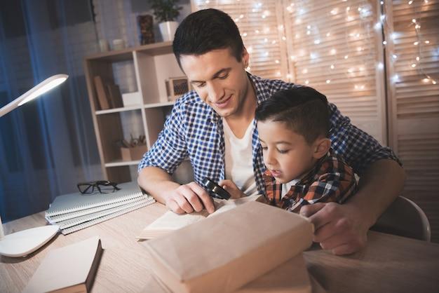 Vader en zoon lezen boek met vergrootglas aan tafel.