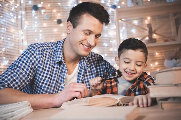 Vader en zoon lezen boek met vergrootglas.