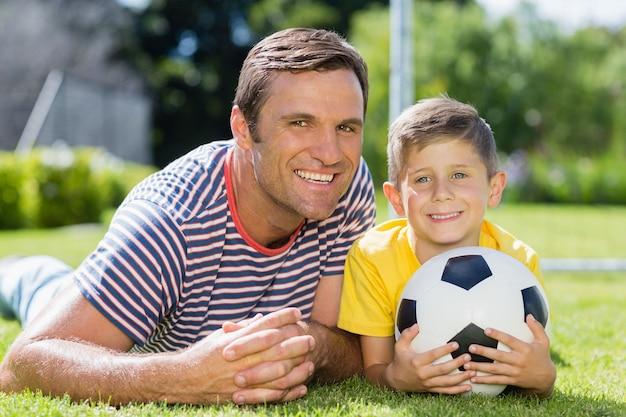 Vader en zoon liggen op gras in het park op een zonnige dag