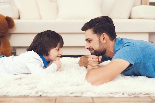 Vader en zoon liggen thuis op tapijt.