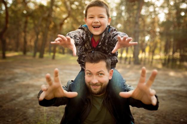 Vader en zoon lopen en hebben plezier in het herfstbos, zien er gelukkig en oprecht uit
