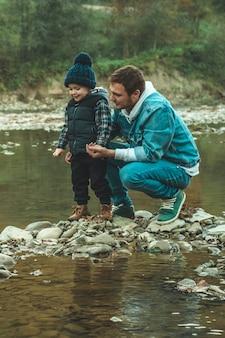 Vader en zoon lopen en spelen samen. de herfst in de bergen.