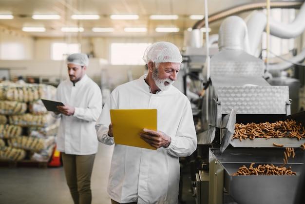 Vader en zoon lopen in steriele kleren door hun voedselfabriek. aantekeningen maken over voedselkwaliteit en er tevreden uitzien.