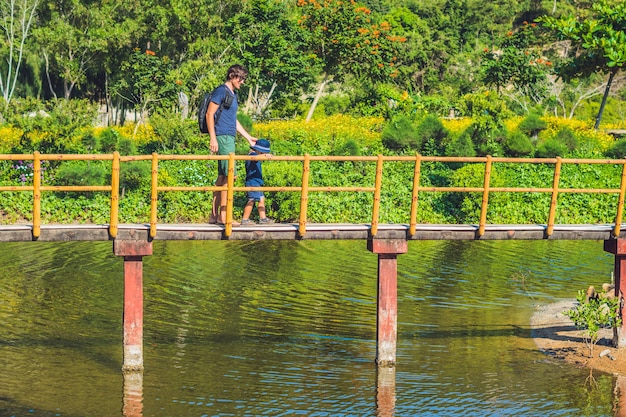 Vader en zoon lopen langs de brug over de vijver. reizen met kinderen concept