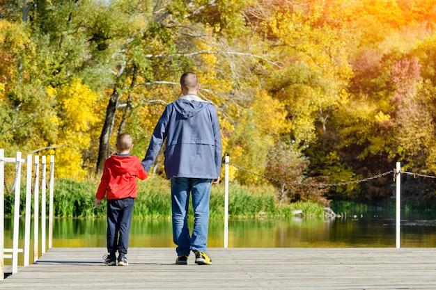 Vader en zoon lopen langs de pier. herfst, zonnig. achteraanzicht