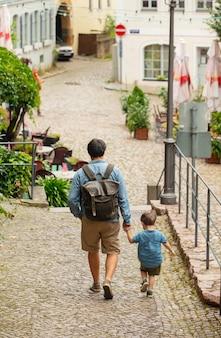 Vader en zoon lopen langs de straat van de oude stad in europa, duitsland