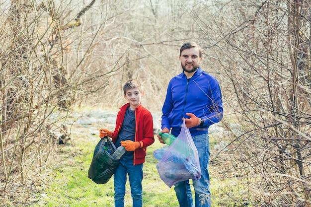Vader en zoon maken het vuilnispark schoon vrijwilligers maken het bos schoon van plastic flessen en brengen samen tijd door