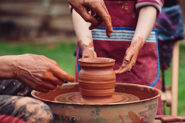 Vader en zoon maken keramische pot. familie bezig met aardewerk wiel. pottenbakkers en kinderhanden. aardewerk workshop buiten. beheers het kind om te creëren op het aardewerkwiel. ambachtsman handen en kind