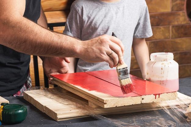Vader en zoon maken samen een houten vogelhuisje in de werkplaats
