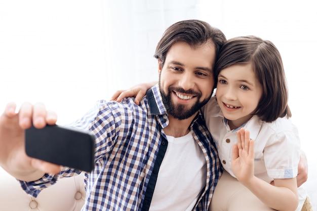Vader en zoon maken thuis selfie op telefoon.