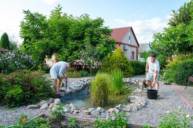 Vader en zoon maken tuinvijverbodem schoon met hogedrukreiniger van modder
