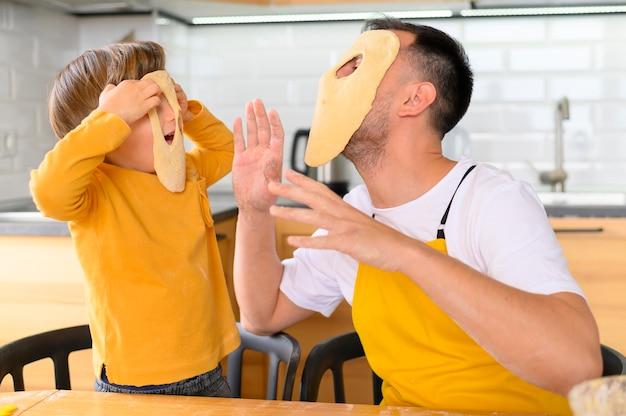 Vader en zoon maskers maken van deeg