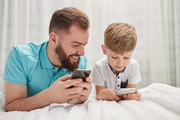 Vader en zoon met behulp van gadgets in de slaapkamer