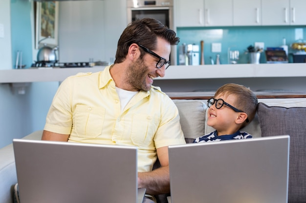 Vader en zoon met behulp van laptops op de bank