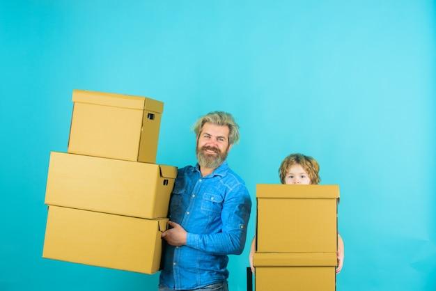 Vader en zoon met dozen vader met zoon die dozen draagt op verhuisdag zoon helpt zijn vader