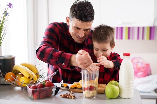 Vader en zoon met gezamenlijke krachten vullen de blenderkom met fruit in lichte keuken.
