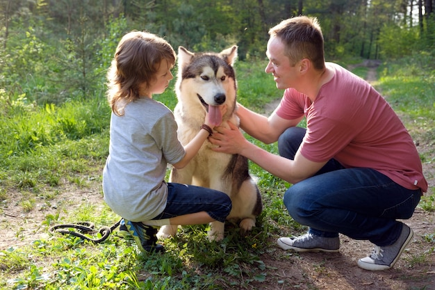 Vader en zoon met hun hond malamute op een wandeling in het bos