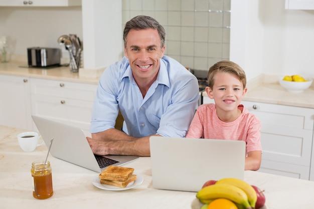 Vader en zoon met laptop in de keuken