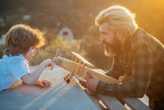 Vader en zoon met speelgoedvliegtuig dromen van reizende vader speelt met kind droom van vliegende vader...