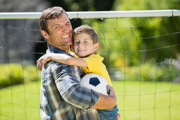 Vader en zoon met voetbal in het park op een zonnige dag