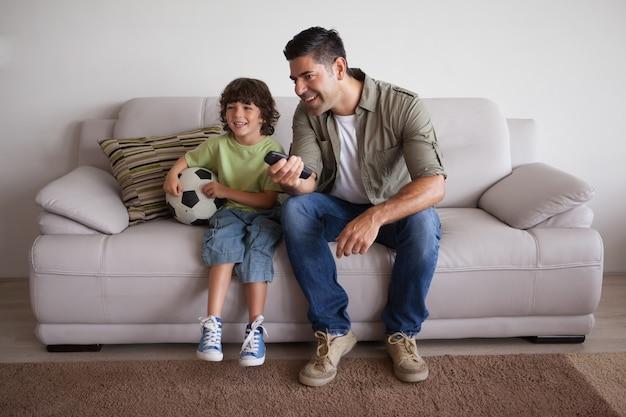 Vader en zoon met voetbal tv kijken in de woonkamer