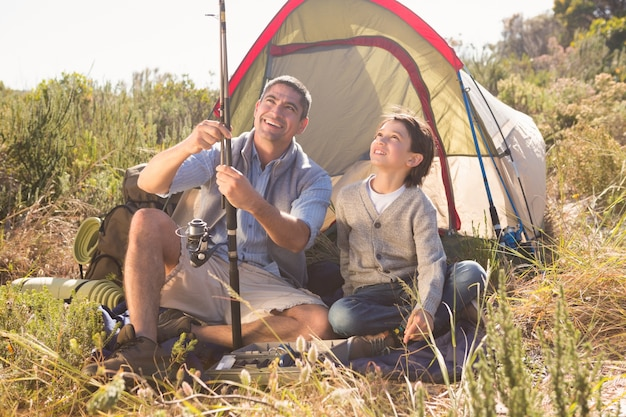 Vader en zoon naast hun tent op het platteland