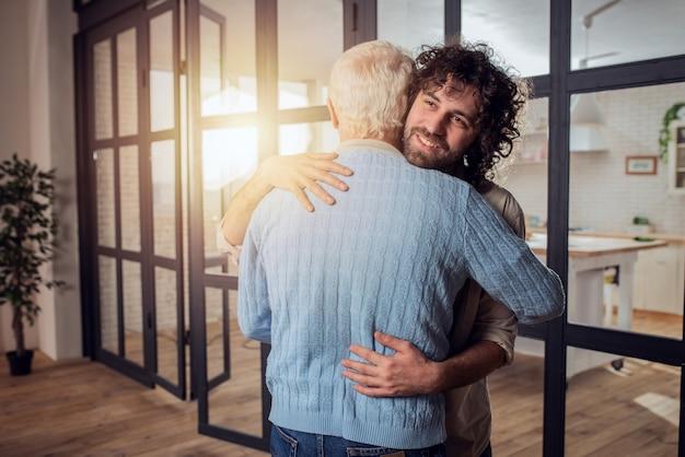 Vader en zoon omhelzen elkaar thuis. concept van familierelatie