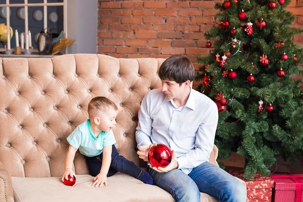 Vader en zoon op een met kerst versierde kamer