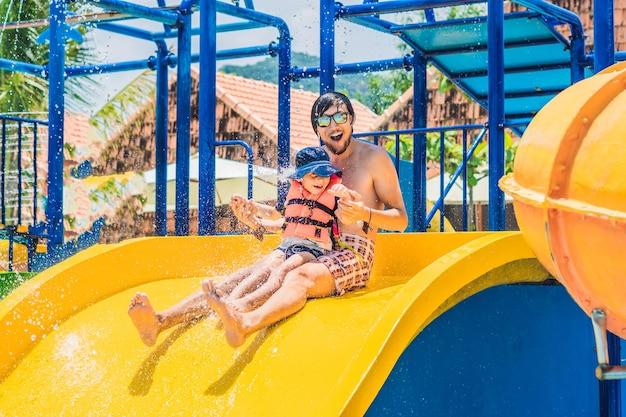 Vader en zoon op een waterglijbaan in het waterpark.
