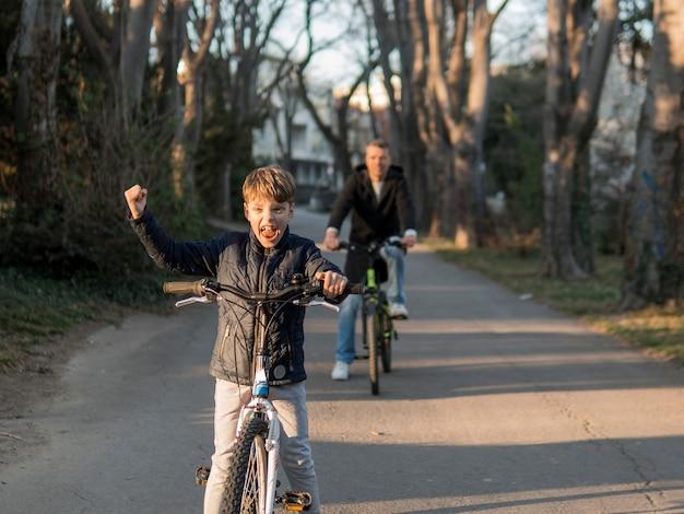 Vader en zoon op fietsen in het park