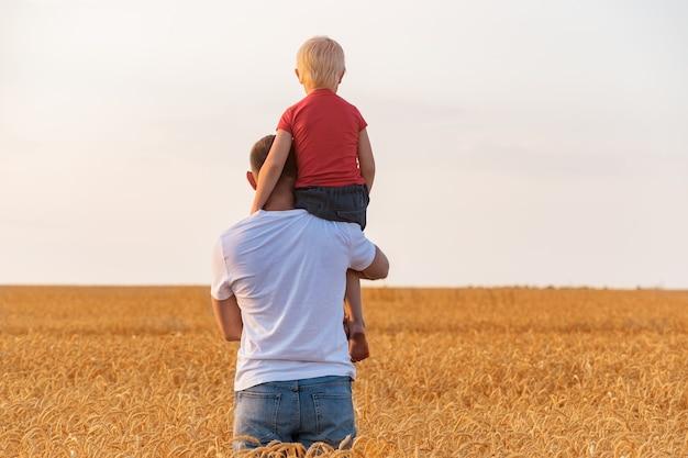 Vader en zoon op gebied van rijpe tarwe. vaderdag. generatie concept.
